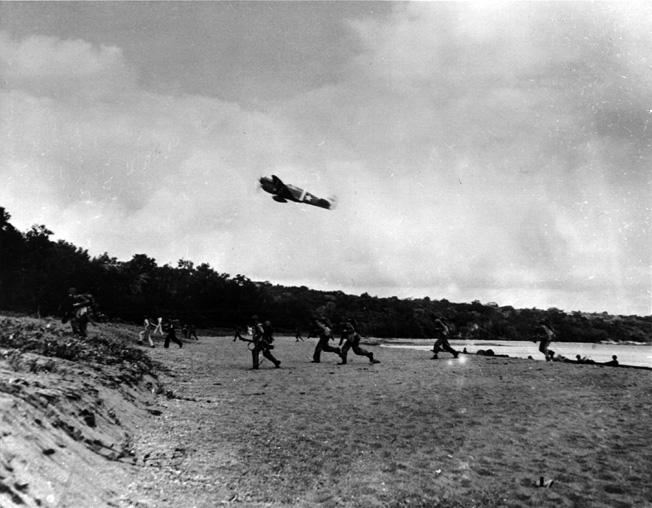 Providing aircover for troops landing at Rendova, a P-40 Tomahawk fighter sweeps low over the invasion beach.
