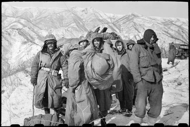 Wounded 7th Infantry Division soldiers and Marines await evacuation during the harrowing retreat from the Chosin Reservoir.