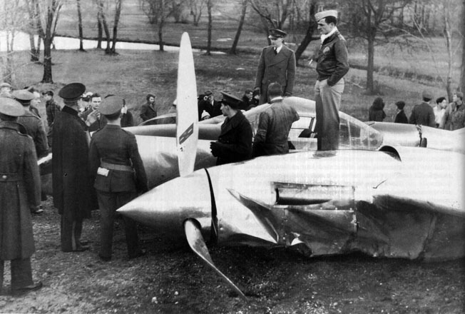 Air Force personnel and curious onlookers gather around a Lockheed XP-38 that crashed during a transcontinental flight on February 11, 1939, onto a Long Island golf course due to carburetor icing. The pilot survived.