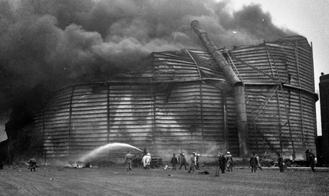 Smoke billows from a 20-million-gallon natural-gas storage tank in Chicago after a B-24 crashed into it on May 20, 1943, killing all 12 men aboard.