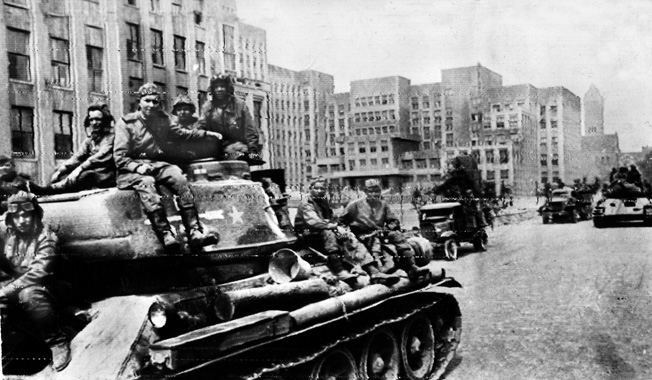 Victorious Soviet soldiers riding on tanks and trucks parade past the government building in Minsk, the capital of White Russia. Minsk was liberated on the 11th day of Operation Bagration.