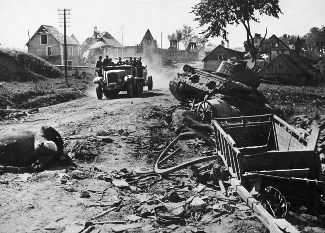 A German 8-ton semitrack Sd. Kfz. 7 troop prime mover hauls several soldiers and an antitank gun past a wrecked Russian T-34 tank near Madona/Latvia in August 1944.