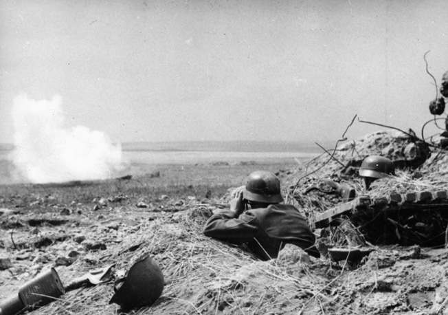 A German soldier watches through binoculars as an antiartillery shell explodes in front of his field position.