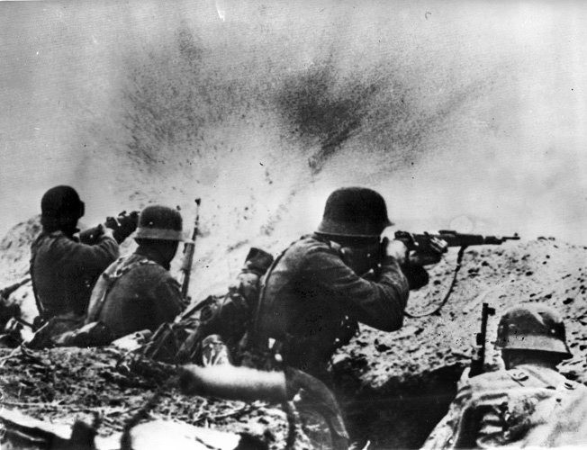 A shell bursts on the parapet of a German trench as a detachment of infantry fires at advancing Soviet assault troops on the southern Russian front.