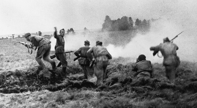 Soviet infantrymen charge out of a trench in Belorussia during Operation Bagration.