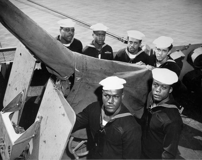 Crewmen of the USS Mason pose by one of the ship's deck guns. The ship was primarily involved in the dangerous business of convoy escort duty in the Atlantic.