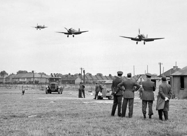 Ground crewmen of Eagle Squadron No. 121 watch as a Supermarine Spitfire Vb.