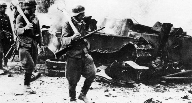 Finnish soldiers of Infantry Regiment JR 12, II Division, advance past the still-smoking wreckage of a Soviet T-34 tank on the Imatra Road in Tali-Ihantala. Some carry German-made panzerfausts, while the soldier in front also carries a Finnish-made Suomi M-31 sub-machine gun.