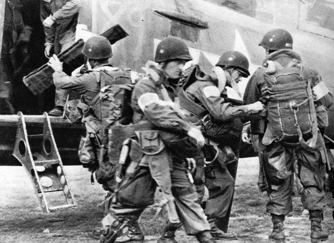 Men of the 82nd Airborne Division check each other's gear before loading onto a Carrier Group C-47 on June 5, 1944.