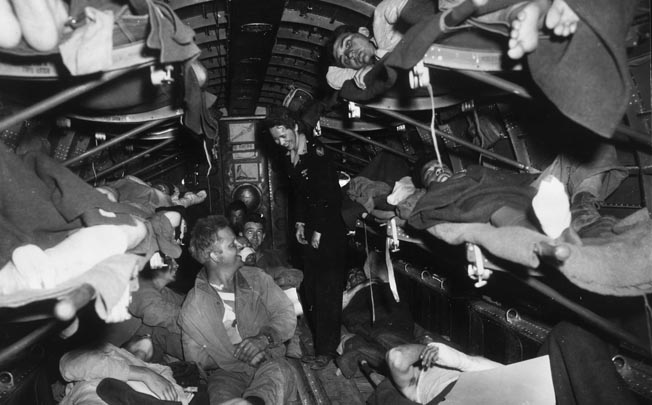 A flight nurse cares for wounded soldiers aboard a C-47 Skytrain transport.