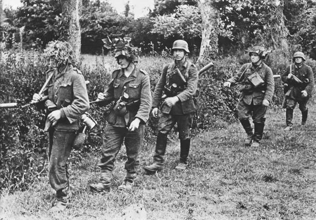 Wearing camouflage on some of their helmets, an unidentified German unit patrols the Normandy countryside. Almost by accident the Germans came across the Americans holed up at Graignes.