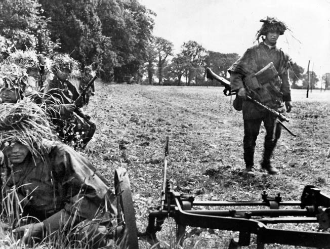One panzergrenadier carries an MG-43 while his comrades conceal themselves in a French hedgerow prior to an assault.
