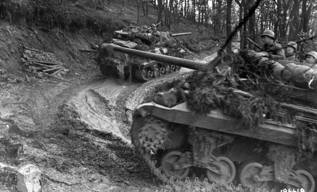 American M-10 tank destroyers crawl up a muddy road through the forest. The narrow, twisting roads and thick stands of trees made the use of armor all but impossible.