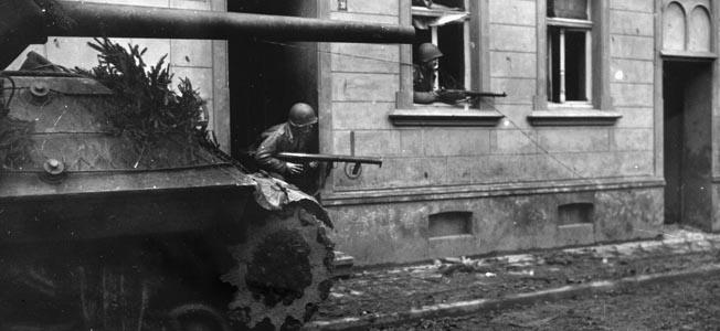 American tank destroyer creeps forward along a cobblestone street.