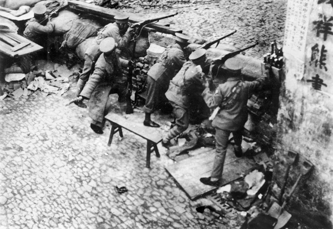 Chinese soldiers manning a quickly constructed barrier in Shanghai await the onslaught of the Japanese. After the bombing of the railway in Mukden on September 18, 1931, Japanese aggression against China increased.
