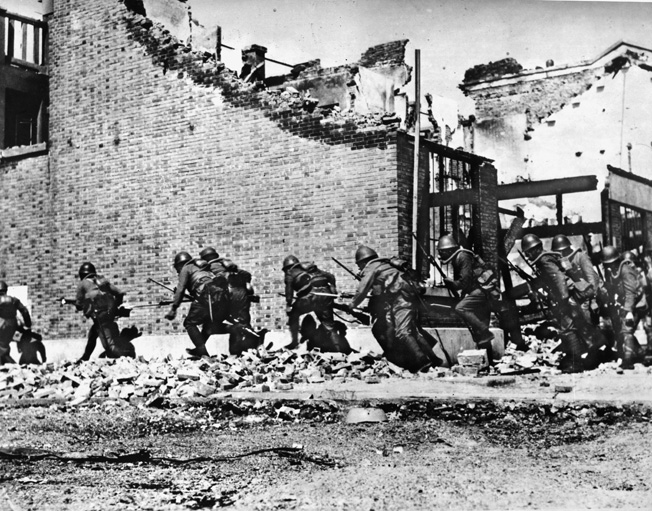 With bayonets at the ready, a Japanese landing party rushes along a crumbing wall as it advances on a Chinese position in Zhabei.