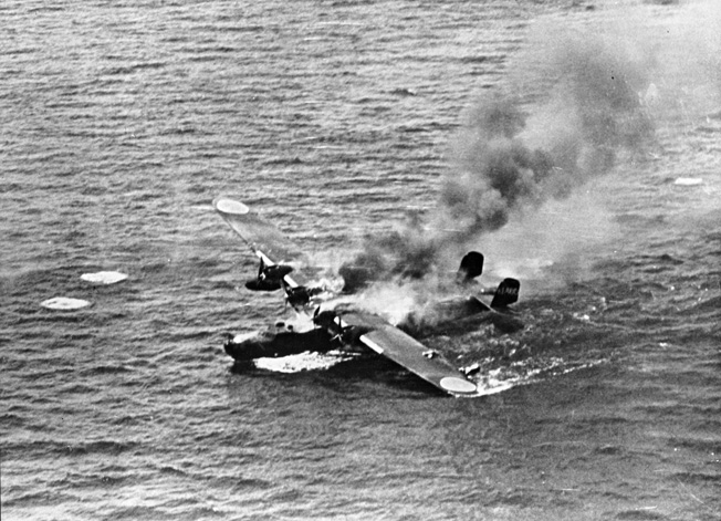 A Kawanishi H6K4 Mavis is engulfed in flames after being shot down by American pilots.
