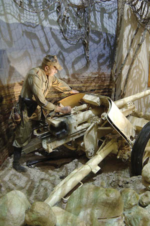 In the North Africa Gallery, a German Afrika Korps mannequin mans an antitank weapon.