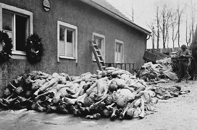 An American soldier surveys a pile of corpses outside the Buchenwald crematorium.