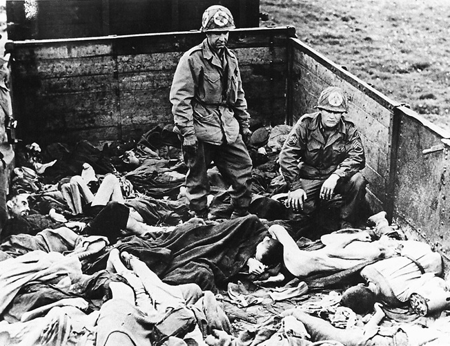 American medics check for signs of life in a railroad car left on a siding outside the Dachau concentration camp, April 29, 1945. Over 2,300 dead victims were found on the train, which had come from Buchenwald.