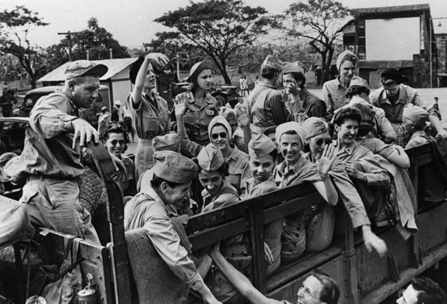 Happy nurses, recently liberated from the San Tomas Internment Compound, smile and wave from an Army truck. They had been taken prisoner by the Japanese after the fail of Bataan and Corregidor.