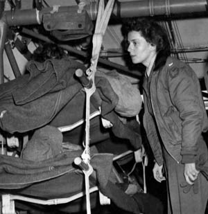 Army flight nurse Lieutenant Suella Bernard tends to patients in one of two CG-4A gliders waiting for a C-47 transport to tow them to a military hospital in France. Bernard became the only nurse known to have participated in a glider combat mission during World War II.