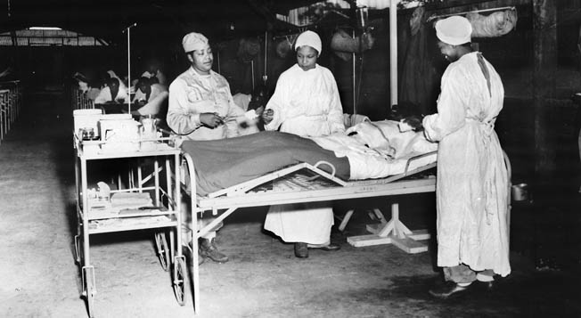 Because the U.S. military was segregated during the war, sick and wounded black patients were tended to by black medical personnel. Here, African American nurses in a surgical ward at the 268th Station Hospital, Base A, Milne Bay, New Guinea, look after a patient.