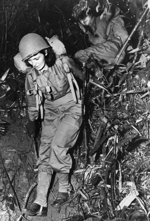 Two American nurses carry heavy combat packs on an eight-mile hike through the jungle of the India-Burma border area as part of their training before taking up frontline war assignments.