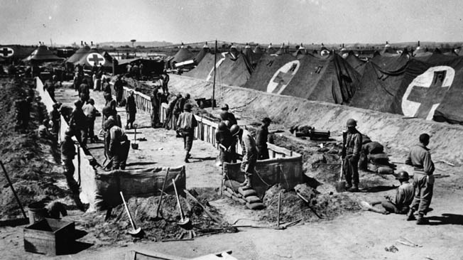 Army personnel prepare to build a tent in the huge hospital area at Anzio. Within range of German artillery, the Anzio beachhead hospitals were continually being hit, causing loss of life to doctors, nurses, and patients.