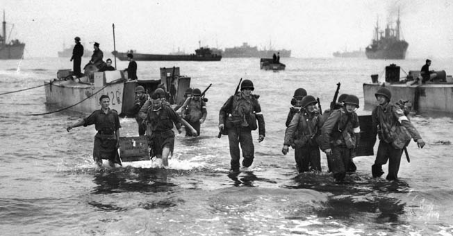 During the Operation Torch landings, November 1942, American personnel carrying heavy medical equipment come ashore at Arzew, Algeria, to help set up the 48th Army Surgical Hospital.