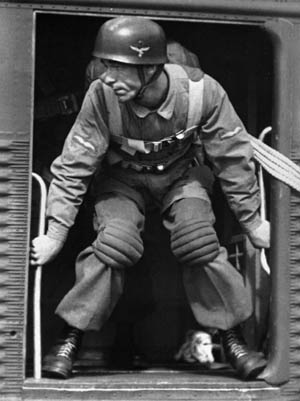 A Fallschirmjäger poses for a publicity shot in the doorway of a Ju-52. Note that the Germans were not equipped with a reserve parachute as American paratroopers were.