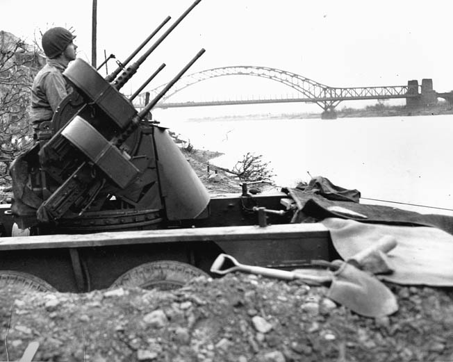 Maintaining a vigil against German aircraft intent on attacking the Ludendorff Railroad Bridge at Remagen, Pfc. Richard Schrame scans the sky and stands ready to spring into action with his quad .50-caliber antiaircraft machine gun.