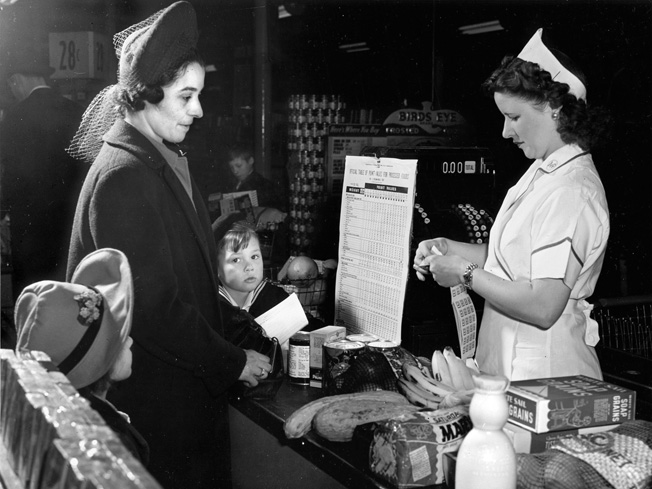 A shopper and her children watch as a clerk tears point stamps from a War Ration Book 2 to cover the processed foods being purchased.