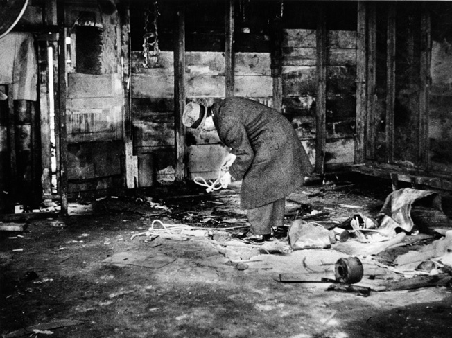 An inspector looks at evidence of a Black Market meat operation in a filthy building. The black marketeers spread lime on the floor in a poor attempt at cleanliness.