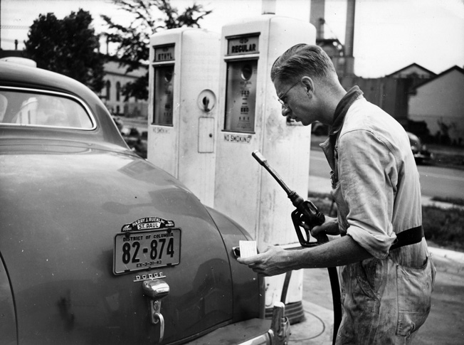 A service station attendant measures out the precious fluid in accordance with OPA's A gasoline ration books, July 1942.