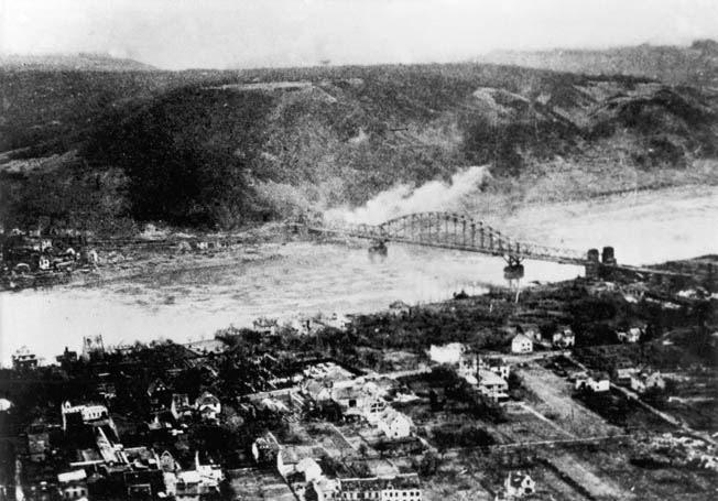 The Ludendorff Railroad Bridge at Remagen comes under fire from German artillery on the eastern bank of the Rhine after its capture by elements of the U.S. 9th Armored Division on March 7, 1945.