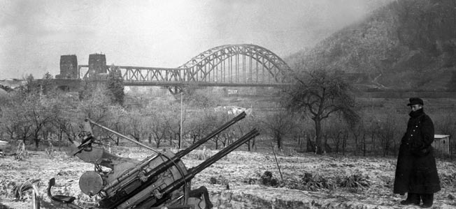 Bundled against the cold of late winter, a German soldier contemplates a 20mm antiaircraft gun emplacement on the banks of the Rhine River. The Ludendorff Railroad Bridge with its great arch looms in the background. This photo was taken in January 1945, two months before American troops and tanks of the 9th Armored Division captured the bridge.