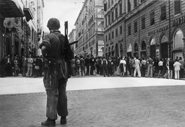 Once allies, now enemies: A German paratrooper stands guard outside the Italian Ministry of Internal Affairs in Rome after Italy capitulated in September 1943.