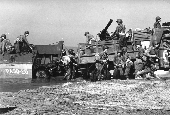 After the initial invasion, U.S. reinforcements arrive at Salerno. Note the steel matting on the sand to facilitate the off-loading of vehicles.