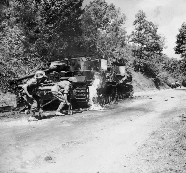 Men of the 2/6th Queen's Regiment advance past a burning German PzKpfw IV tank in the Salerno area, September 22, 1943.