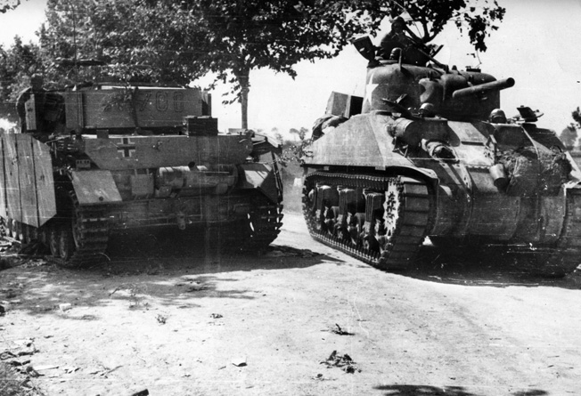 A Sherman tank of the U.S. Fifth Army moves inland after landing at Salerno, passing a German tank knocked out of action during fighting in the area.