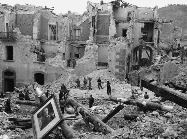 Civilians of Eboli, Italy, work to clear the rubble of their town, left in ruins by the fierce fighting. Note the photo of Mussolini in the foreground.