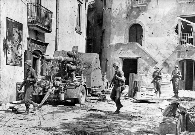U.S. infantry moves through the square at Acerno after breaking out from the beachhead. The tenacious defense shown by the Germans at Salerno was no match for the overwhelming resources of the Allies.