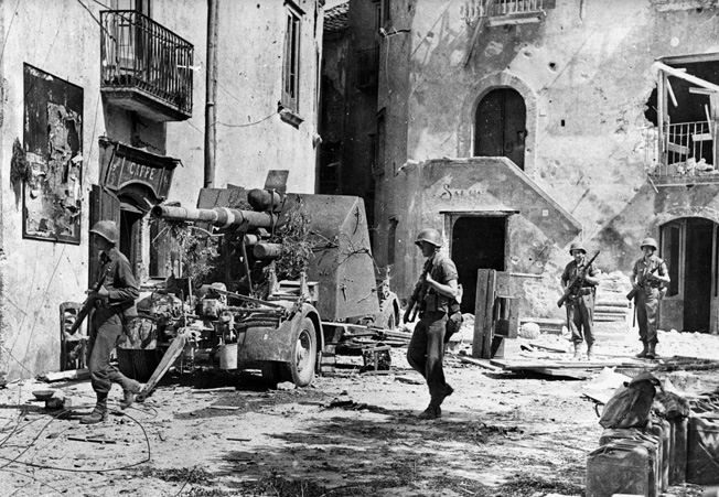American troops enter the ruined square at Acerno, 14 miles northeast of Salerno, as the Germans retreat northward.