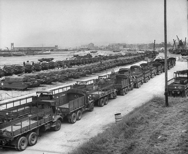 Hundreds of military vehicles brought over from England are lined up on the beach near the recently repaired Cherbourg harbor, summer 1944.