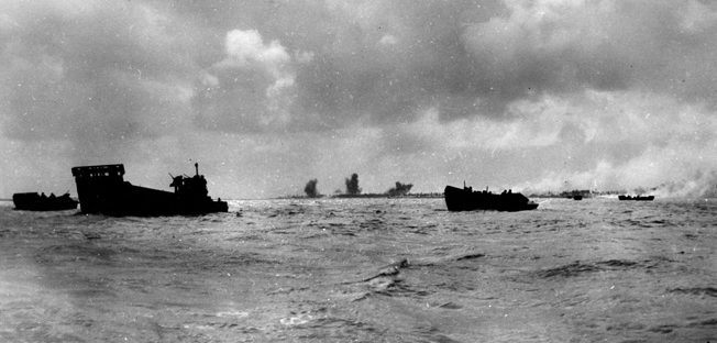 """While Betio, the principal island of the Tarawa Atoll (background), takes a pounding from naval gunfire, landing craft circle in anticipation of the order to """"Land the landing force,"""" November 20, 1943."""