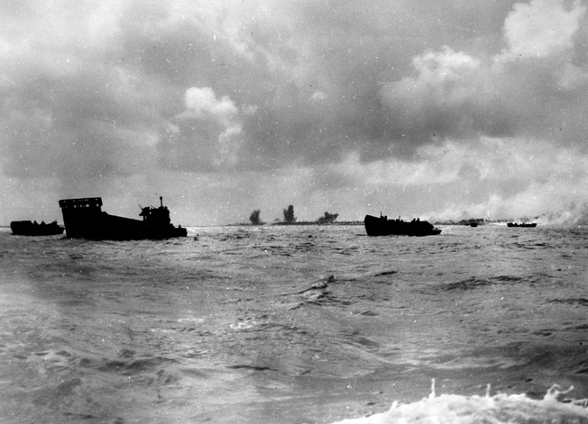 "While Betio, the principal island of the Tarawa Atoll (background), takes a pounding from naval gunfire, landing craft circle in anticipation of the order to ""Land the landing force,"" November 20, 1943."