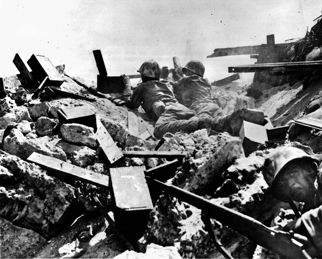 Fear is etched on the face of a Marine (foreground) while a machine-gun team pours fire into the enemy from the rubble of a destroyed Japanese position.