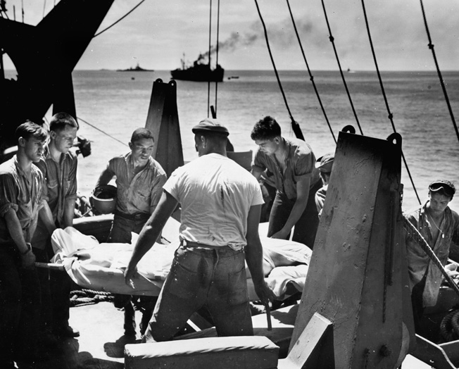 Navy medical personnel aboard a ship gently handle a casualty from the fighting on Tarawa. The wounded will soon be bound for naval hospitals in Hawaii and then California.