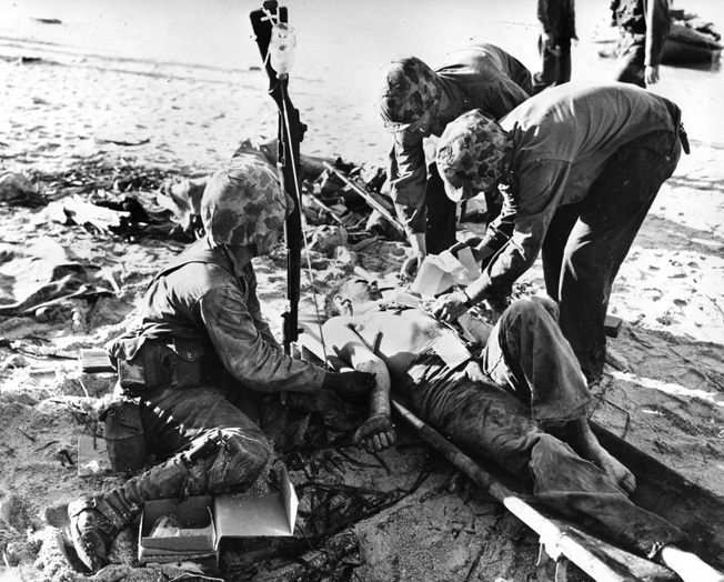 While a rifle is used to hang a bottle of plasma, a wounded Marine receives medical care on the sands of Tarawa.